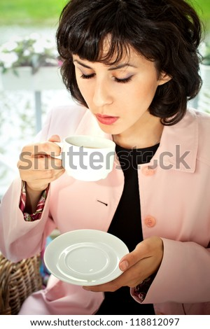 Young woman drinking coffee  in the cafe open air - stock photo