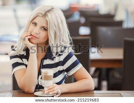 Young woman drinking coffee latte in a trendy cafe. woman drinking coffee in the morning at restaurant.  - stock photo