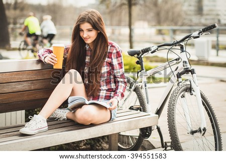 Young woman drinking coffee on a bicycle trip. - stock photo
