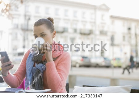 Young woman drinking coffee while using cell phone at sidewalk cafe - stock photo