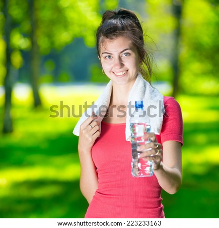 Young woman drinking cold mineral water after sport fitness exercise at green summer park - stock photo