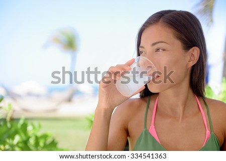 Young woman drinking fresh water or lime juice at beach. Female is looking away while sitting at outdoor restaurant. Beautiful tourist is having healthy drink during summer vacation. - stock photo