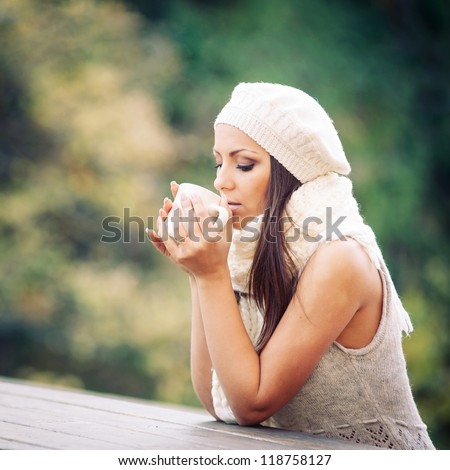 Young woman drinking from a cup outdoors in the nature. - stock photo