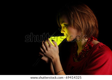 young woman drinking from a glass of glowing liquid - stock photo