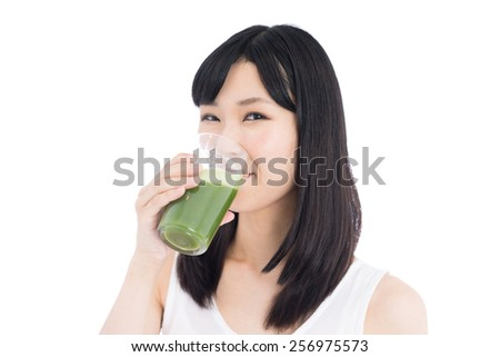 young woman drinking green vegetable smoothie, isolated on white background - stock photo