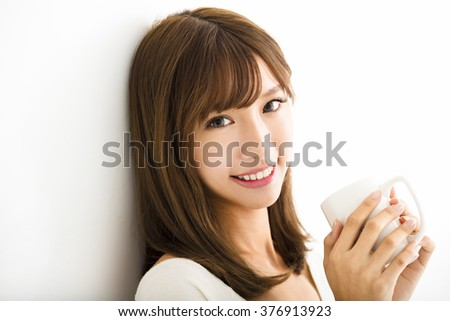 young Woman drinking hot latte coffee in living room - stock photo