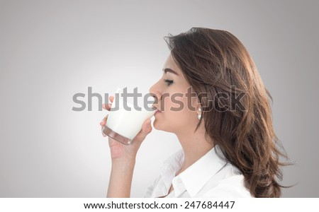 young woman drinking milk,gray background - stock photo