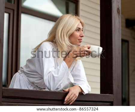 Young Woman Drinking Morning Coffee on Porch - stock photo