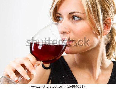 Young woman drinking red wine - studio shot - stock photo