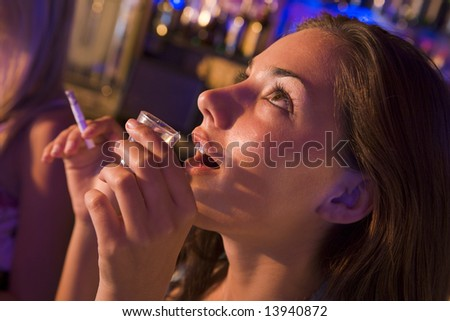 Young woman drinking shots and smoking at a nightclub - stock photo
