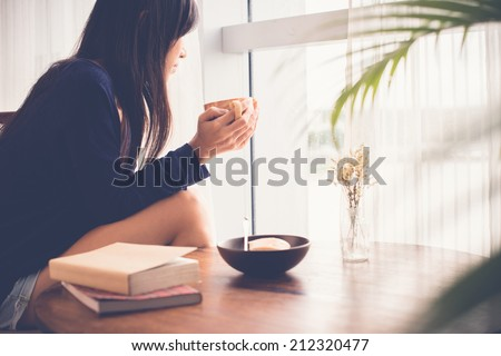 Young woman drinking tea and looking out of the window - stock photo