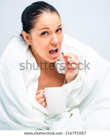 young woman drinking tea in bed at home - stock photo