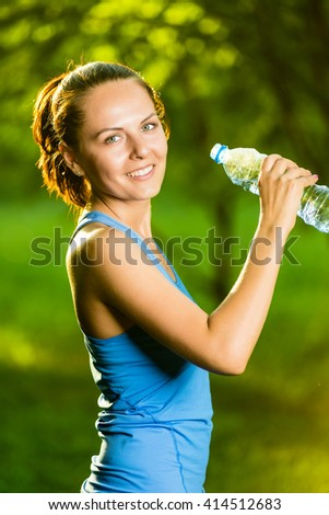 Young woman drinking water after fitness exercise. Cold drink  at summer green park. Outdoor sport - stock photo