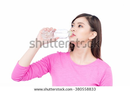 Young woman drinking water after jogging. Beautiful girl portrait. Female model poses. - stock photo