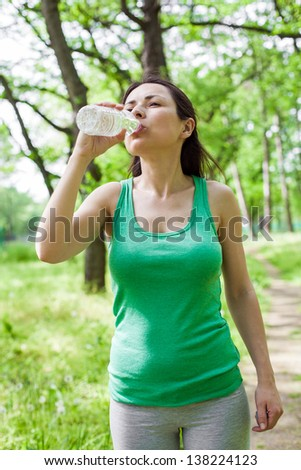 Young woman drinking water at park after exercising - stock photo