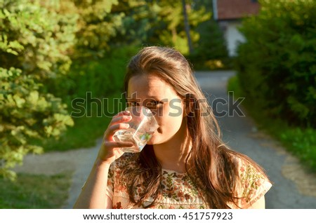 Young woman drinking water from the glass, in the park. Healthy lifestyle. Prevention of dehydration. - stock photo