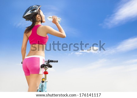 Young woman drinking water with folding bike - stock photo