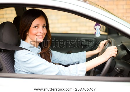 young woman drinving her car wearing her seatbelt. - stock photo