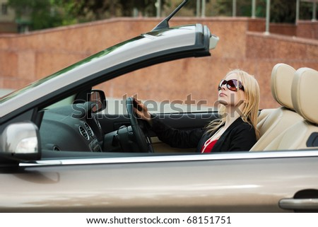 Young woman driving a convertible car. - stock photo