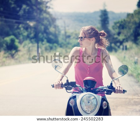 young woman driving a scooter, with a retro image toning - stock photo