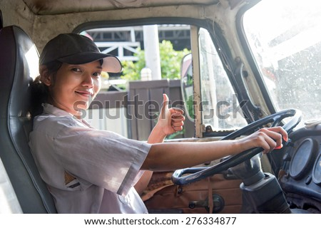 young woman driving a truck with thumb up. Woman driving trucks. The truck driver shows gesture thumbs-up. Happy Asian woman driving a car with a gesture of success. Driver inside of used old lorry. - stock photo