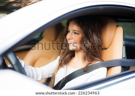 Young woman driving her car - stock photo