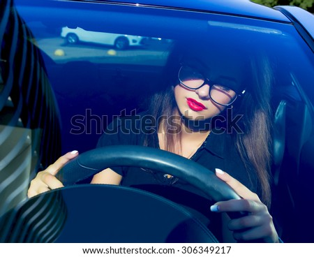 Young woman driving her car.Stylish student girl in car.Summer fashion close up portrait of elegant beautiful woman driving her car in urban city, wearing black shirt and black clear glasses. - stock photo