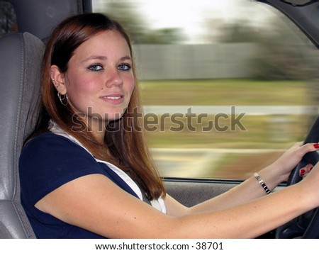 young woman driving in a car - stock photo