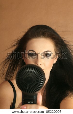young woman drying her hair electric hair dryer - stock photo