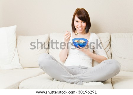 Young woman eating a bowl of muesli in her living room - stock photo