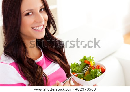 Young woman eating a salad - stock photo
