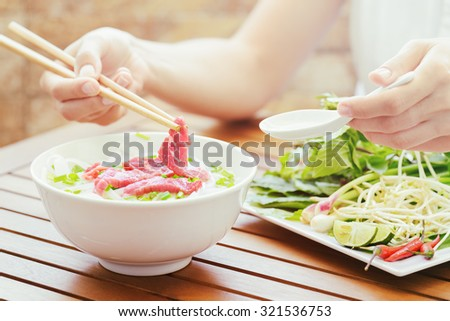 Young woman eating and enjoying the Pho Bo in street cafe of Vietnam. The Pho Bo is a traditional Vietnamese beef noodle soup with garnish of leaves of cilantro and Asian basil. Healthy street food. - stock photo