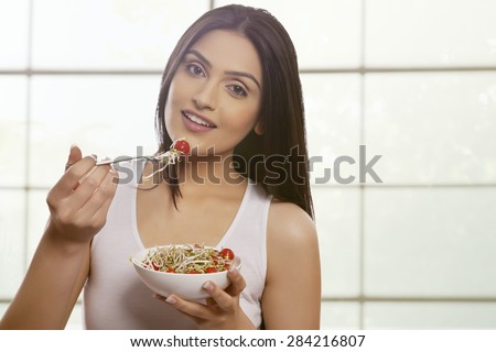Young woman eating bean sprouts and cherry tomatoes against glass window - stock photo