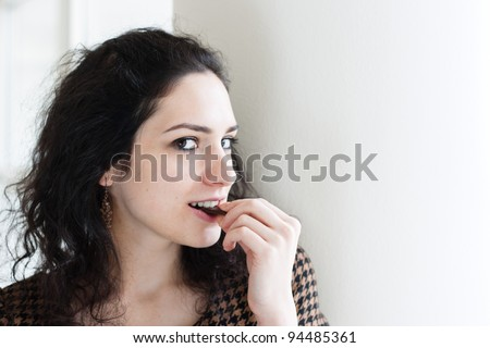 Young woman eating chocolate against white background - stock photo