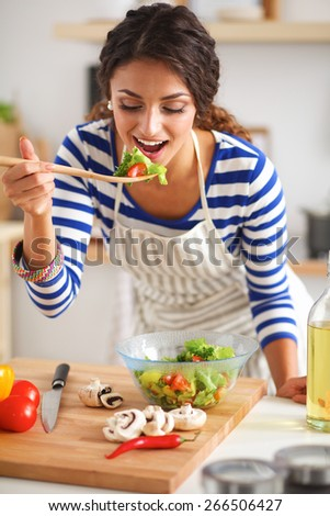 Young woman eating fresh salad in modern kitchen - stock photo