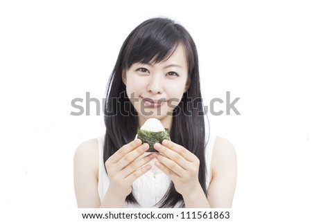"""young woman eating Japanese rice ball """"onigiri"""", isolated on white background - stock photo"""