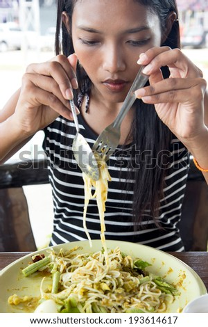young woman eating noodles - stock photo