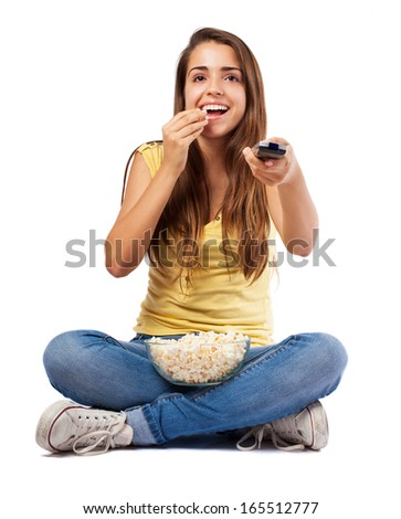 young woman eating popcorn and watching the tv on white - stock photo
