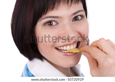 Young woman eating potato chips. Lovely girl eating potato chips. Eating potato chips / crisps. Cute woman having a junk food snack while looking up at camera - stock photo