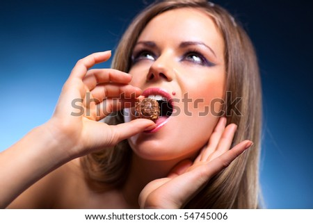 Young woman eating sweet portrait. Focus on sweet. - stock photo