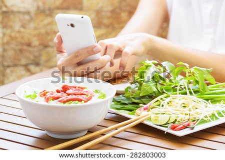 Young woman eating the Pho Bo and using smartphone in street cafe of Vietnam. The Pho Bo is a traditional Vietnamese beef noodle soup with garnish of leaves of cilantro and Asian basil. Popular food. - stock photo