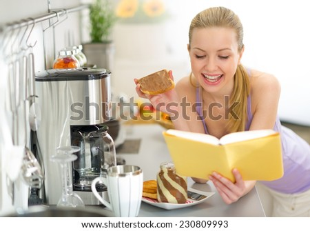 Young woman eating toast with chocolate cream and reading book - stock photo