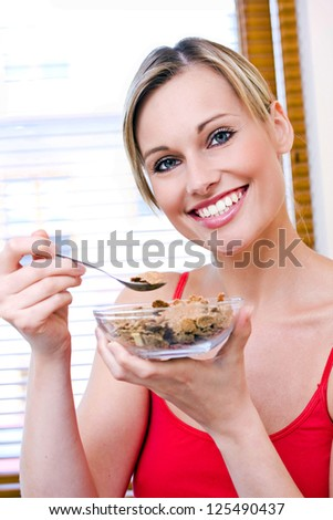 Young woman eats cereal - stock photo