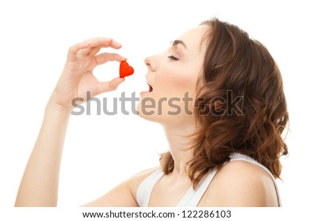 Young woman eatting candy heart isolated on white - stock photo
