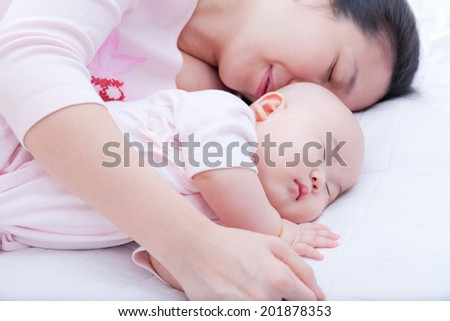 Young woman embrace her newborn daughter sleeping in the bed - stock photo