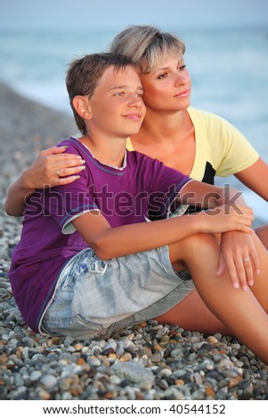 young woman embraces smiling boy on beach in evening, Looking afar - stock photo