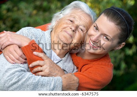 Young woman embracing her grandmother - stock photo
