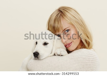 Young woman embracing pet puppy, portrait - stock photo