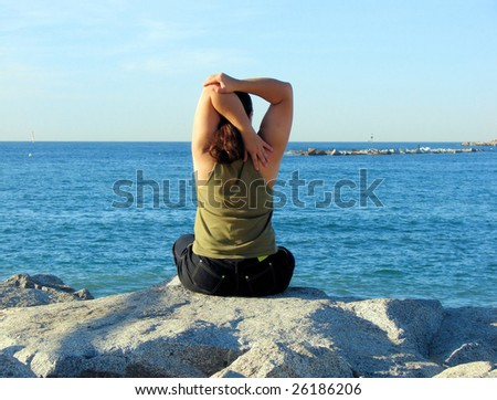 young woman engaged in yoga on  bank of mediterranean sea, spain - stock photo