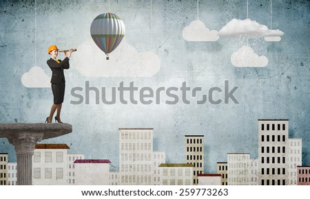 Young woman engineer looking in to spyglass - stock photo